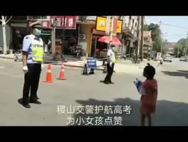高考天气炎热,一小女孩从妈妈手里拿过两瓶水,向民警送去,表达她对交警护航高考的敬意。